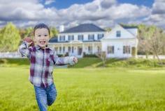 Skämtsam pojke för blandat lopp som kastar en fotboll i hans Front Yard arkivbilder