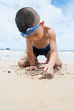Skämtsam pojke på stranden med havet på bakgrund. Royaltyfri Fotografi