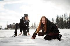 Skämtsam rödhårig mankvinna som kastar snö på hennes man arkivfoto