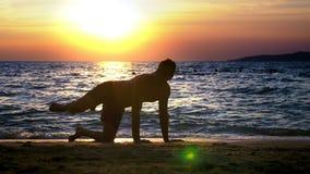 Skämtsam stilig grabb i kortslutningar som gör kondition, på kusten mot bakgrunden av en underbar solnedgång arkivfilmer