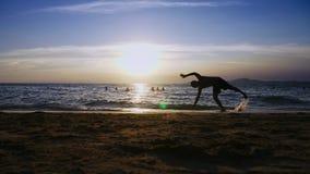 Skämtsam stilig grabb i kortslutningar som gör kondition, på kusten mot bakgrunden av en underbar solnedgång stock video
