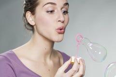 Skämtsam 20-talflicka som blåser såpbubblor för gyckel och fantasi Fotografering för Bildbyråer
