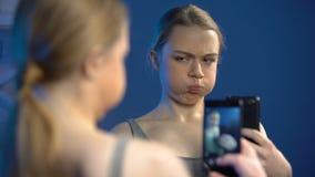 Skämtsam tonåring som gör framsidor som tar selfie vid smartphoneframdelen av spegeln stock video