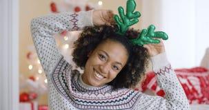 Skämtsam ung kvinna som bär gröna renhorn på kronhjort Royaltyfri Fotografi
