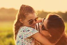 Skämtsam unge i solglasögon som rymmer och omfamnar hennes moder och ser med förälskelse på naturbakgrund kvinna f?r closeupframs royaltyfria foton