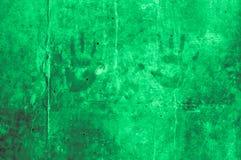 skämtsamma färgrika barnhandintryck på en mintkaramell gör grön grayi Arkivfoto