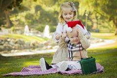 Skämtsamma flickaförsök att sätta Santa Hat behandla som ett barn på brodern arkivfoto