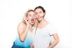 Skämtsamma flickor som poserar på vit arkivfoto