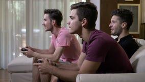 Skämtsamma tonåriga pojkar som sitter på den hemmastadda soffan spela mot varandra den springa leken på konsolen arkivfilmer
