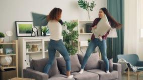 Skämtsamma unga kvinnor afrikansk amerikan och asiat slåss med kuddar som står på soffan och att skratta Flickor är stock video