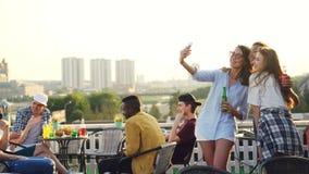 Skämtsamma unga kvinnor tar selfie med smartphonen som gör roliga framsidor som visar tung- och kaninöron som har gyckel stock video