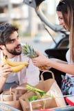Skämtsamma unga par som laddar livsmedelsbutikpåsar in i en bil arkivfoton