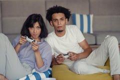 Skämtsamma unga par som spelar videospel i deras vardagsrum arkivfoto