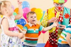 Skämtsamma ungar med clownen på födelsedagdeltagare Fotografering för Bildbyråer