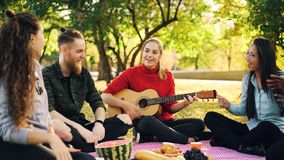 Skämtsamma ungdomarär sjungande, och flyttninghänder, när den härliga flickan skulle spela gitarren under picknick in, parkerar p arkivbilder
