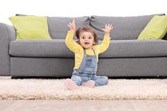 Skämtsamt behandla som ett barn flickan som gör en gest lycka som placeras på golv Royaltyfria Foton