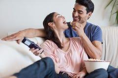 Skämtsamt koppla ihop hållande ögonen på TVstunder som äter popcorn Arkivbilder
