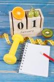 Skära i tärningar kalendern med datumet av 1 Januari, frukter, hantlar och måttbandet, nya år upplösningar Arkivfoton