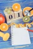 Skära i tärningar kalendern med datumet av 1 Januari, nya frukter, hantlar och måttbandet, nya år upplösningar Royaltyfri Foto