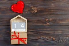 Skära i tärningar kalendern med den röda hjärta- och gåvaasken på trätabellen med kopieringsutrymme 14 Februari begrepp Arkivfoton
