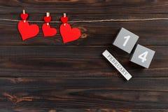 Skära i tärningar kalendern med röda hjärtor på trätabellen med kopieringsutrymme 14 Februari begrepp Arkivfoto