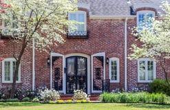 Skära ner detnätta exklusiva tegelstenhuset för två berättelse med den välvda dörren och shtters och skogskornellträd i blom royaltyfria foton