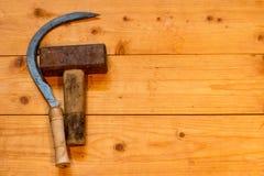 Skära och hammare på en trätabell arkivbilder