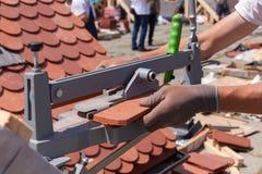 Skärare för tegelplatta för bruk för Rooferbyggmästarearbetare som skapar ett korrekt format av den naturliga röda keramiska tege Arkivbilder