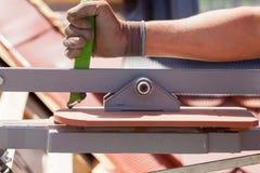 Skärare för tegelplatta för bruk för Rooferbyggmästarearbetare som skapar ett korrekt format av den naturliga röda keramiska tege Royaltyfri Fotografi