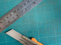 Skärare och linjal på att klippa som är mattt Fotografering för Bildbyråer