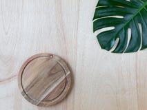 Skärbräda för tropiskt monsterablad och för runt trä på den wood bakgrunden arkivbilder