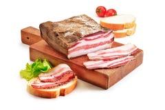 Skärbräda med bacon och bröd Arkivfoto