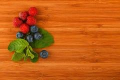 Skärbräda med blåbär, hallon och mintkaramellsidor Royaltyfri Foto