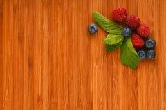 Skärbräda med blåbär, hallon och mintkaramellsidor Royaltyfria Bilder