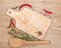 Skärbräda med kryddor omkring över trätabellen royaltyfri foto