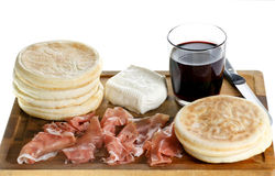 Skärbräda med litet rundalägenhetbröd, skinka, ost och exponeringsglas av rött vin Royaltyfri Foto