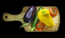 Skärbräda med några grönsaker Royaltyfri Bild