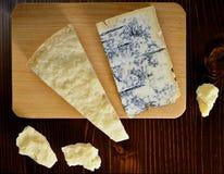 Skärbräda med parmesan och Gorgonzola ost Arkivbild