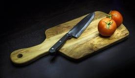 Skärbräda med två tomater Royaltyfri Bild
