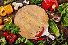 Skärbräda, nya grönsaker och örter på tabellen fotografering för bildbyråer