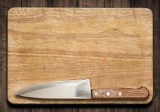 Skärbräda och kniv på den gamla wood tabellen Arkivfoton