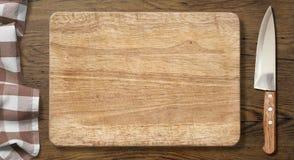 Skärbräda och kniv på den gamla wood tabellen med Arkivbilder