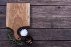 Skärbräda, rosmarin och kryddor på en gammal trätabell kopiera avstånd Begrepp för meny för restaurangkafébistroer Royaltyfria Bilder
