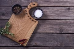 Skärbräda, rosmarin och kryddor på en gammal trätabell kopiera avstånd Begrepp för meny för restaurangkafébistroer Royaltyfria Foton