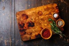 Skärbräda salt, peppar och rosmarin Arkivbild