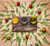 Skärbrädan med kryddor och smör, med arugulasidor runt om stället för text, inramar bästa sikt för trälantlig bakgrund Arkivfoton