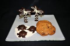 Skärm av chokladsköldpaddor och palmträd på ett socker sätter på land med blandade kakor på en vit glass platta- och svartbakgrun royaltyfri foto