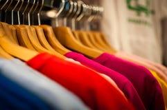 Skärm av färgrika hängande t-skjortor royaltyfria bilder