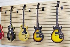 Skärm av gitarrer i ett gitarrlager arkivfoto