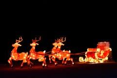 Skärm för ljus för vinterjul dekorativ av jultomtenvagnen med renen royaltyfri foto